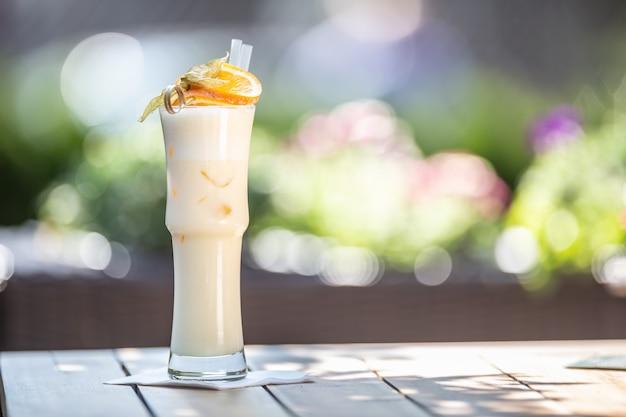 Cocktail pinacolada ou milkshake avec pailles et orange sur le dessus servi dans un verre haut sur une terrasse d'été.