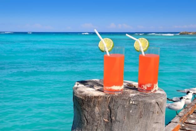 Cocktail de plage orange dans la mer turquoise des caraïbes