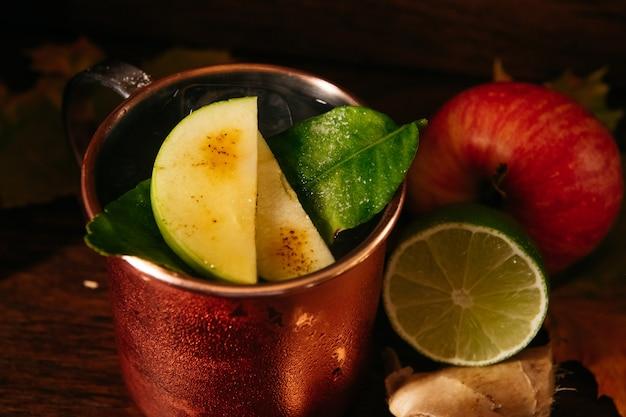 Cocktail de pomme avec glace et citron vert dans une tasse en fer