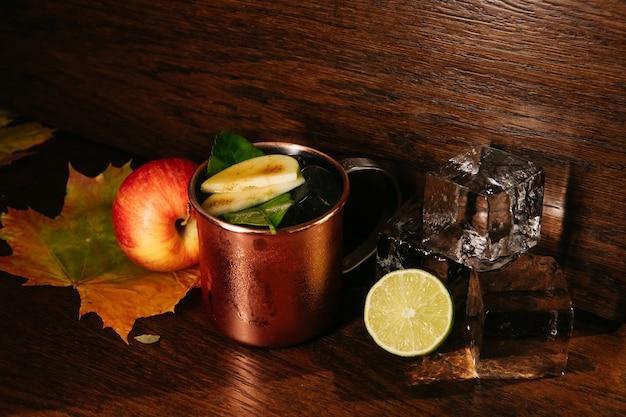 Cocktail de pomme avec de la glace dans une tasse de fer