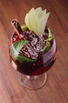 Cocktail de pommes à la cannelle et pommes fraîches en tranches dans un verre à vin sur une table en bois.