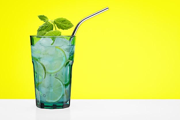 Cocktail rafraîchissant aux agrumes et un brin de menthe dans un grand verre bleu