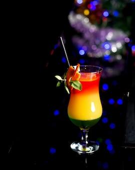 Cocktail rafraîchissant décoré de zeste d'orange et de feuilles de menthe