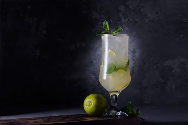 Cocktail rafraîchissant à la lime avec de la menthe et de la glace sur un fond sombre. boisson gazeuse au citron vert et à la menthe. fermer.