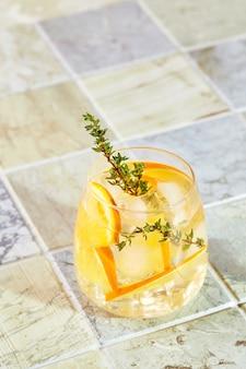 Cocktail rafraîchissant à l'orange glacée et au thym cocktail d'été rafraîchissant fait maison avec ou sans alcool ou mocktail ou eau aromatisée infusée détox