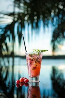 Cocktail de raisin sur fond tropical