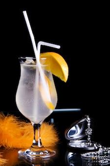Cocktail réfrigéré longdrink en verre et décoration sur fond noir.