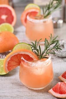 Cocktail rose palomas citron vert frais et romarin combiné avec du jus de pamplemousse frais et de la tequila.