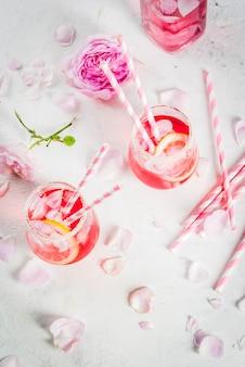 Cocktail rose rose clair, avec vin rosé, pétales de rose thé et citron sur une table en béton de pierre blanche.