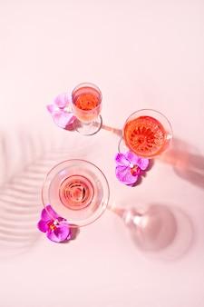 Cocktail rose tropical d'été dans différents verres décorés de fleurs d'orchidées roses. vue de dessus.