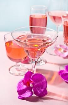 Cocktail rose tropical d'été dans différents verres décorés de fleurs d'orchidées roses.