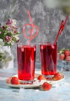 Cocktail rouge fraise avec de la glace avec de la paille