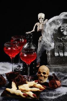 Cocktail sanglant avec de la glace sur la table avec une collation de biscuits aux doigts de sorcière en l'honneur d'halloween.