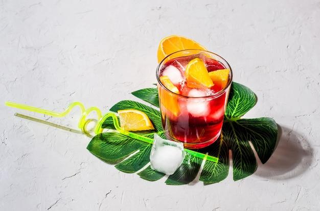 Cocktail de sangria rouge froid avec orange et glace en verre
