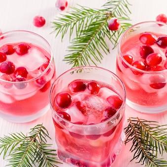 Cocktail sans alcool d'hiver avec canneberge et glace sur fond de bois, gros plan, vue de dessus