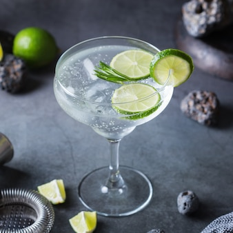 Cocktail de seltz dur avec citron vert, romarin et glace sur une table. boisson rafraîchissante d'été, boisson