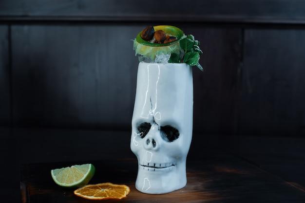 Cocktail sucré tropical avec: tequila, rhum blanc, morceaux de fruits et feuilles de menthe sur une table en bois dans le bar. délicieux cocktail alcoolisé dans le verre crâne blanc d'origine.