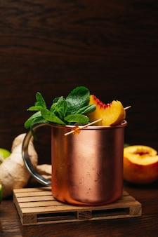 Cocktail en tasse de fer avec menthe pêche citron vert et gingembre