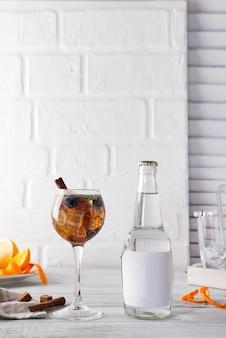 Cocktail avec thé glacé, whisky, baies et glace dans un verre avec une bouteille de tonique