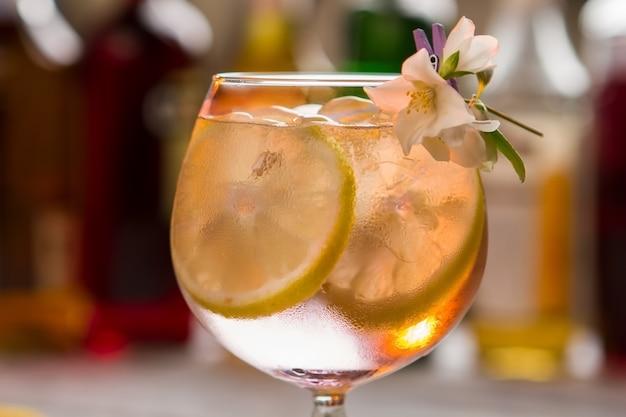 Cocktail avec tranche de citron. glace et petite fleur. tom collins servi au bar. gin et eau gazéifiée.