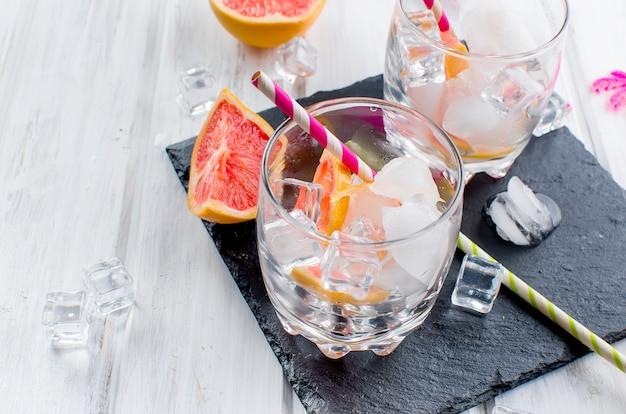 Cocktail avec une tranche de pamplemousse sur une table en bois