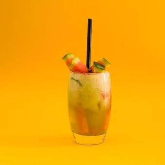 Cocktail avec une tranche de pastèque sur fond jaune
