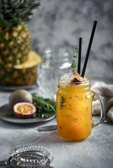 Cocktail tropical aux fruits de la passion, citron vert et menthe sur une surface grise
