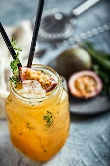 Cocktail tropical frais avec orange, pêche et fruit de la passion