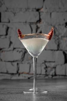 Cocktail en verre avec piment sur surface grise. boisson alcoolisée du diable.