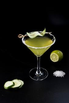 Cocktail vert avec brochette de concombre, sel, citron vert et tranches de concombre sur fond noir