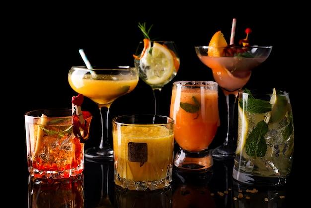 Cocktail whisky-cola, cocktail au mojito, cocktail à l'orange, cocktail à la fraise dans des verres en verre