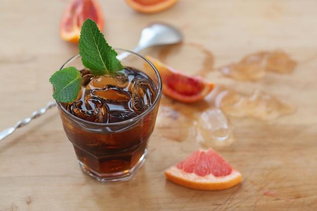 Cocktail whisky cola avec de la glace dans un verre. sur une planche de bois, des fragments de fruits. photo avec profondeur de champ.