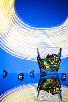 Un cocktail de whisky dans un verre avec des glaçons d'effets de lumière concept fête sur bleu