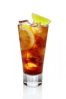 Cocktail de whisky avec du cola, de la glace, du citron et du citron vert dans un verre à whisky isolé sur blanc.