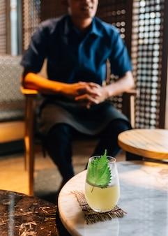 Cocktail de yuzu japonais avec des feuilles de shiso (perilla verte) dans un verre sur une table basse en marbre avec un mixologue en arrière-plan flou.