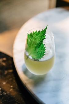 Cocktail de yuzu japonais avec feuilles de shiso (perilla verte) dans un verre sur une table en marbre.