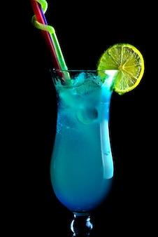 Cocktails alcoolisés bleus sur fond noir, dans un grand verre
