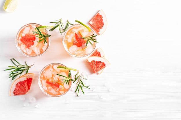 Cocktails alcoolisés paloma avec tequila et glace garnie de quartiers de citron vert pamplemousse
