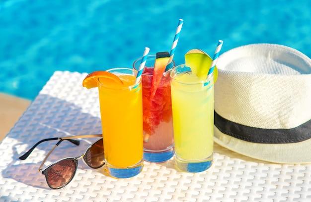 Cocktails, chapeau et lunettes de soleil au bord de la piscine