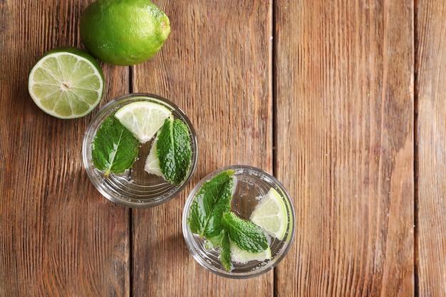 Cocktails frais à la menthe, glace et citron vert sur la surface de la table en bois, vue d'en haut