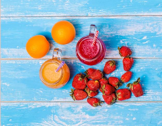 Cocktails fraises et orange frais avec des fruits sur un mur rustique en bois.
