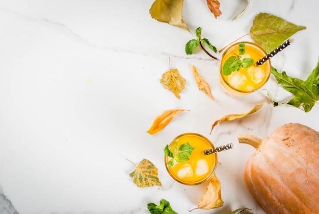 Cocktails froids d'automne et d'hiver. mojito citrouille épicé à la menthe fraîche, sur table en marbre blanc. copie vue de dessus de l'espace