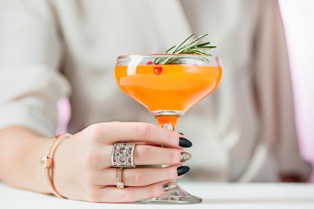 Les cocktails et fruits exotiques à la rose et la main féminine