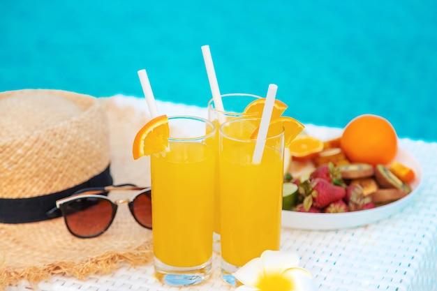 Cocktails, lunettes de soleil, chapeau de paille et fruits frais dans un bol blanc au bord de la piscine