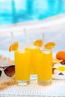 Cocktails, lunettes de soleil et fruits frais dans un bol blanc au bord de la piscine