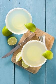 Cocktails margarita au citron vert en verre sur une table en bois bleu, vue du dessus
