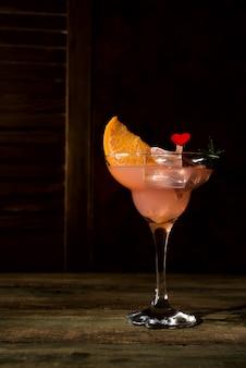 Cocktails margarita glacés dans des verres à pied sur un fond en bois foncé, espace copie