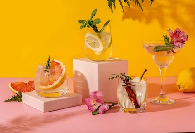 Cocktails de seltz dur avec divers fruits : poire, pamplemousse, citron. boissons d'été colorées rafraîchissantes sur fond jaune avec fougère d'ombre.