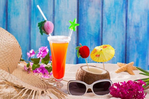 Cocktails tropicaux sur le bois bleu et le sexe de sable sur la plage