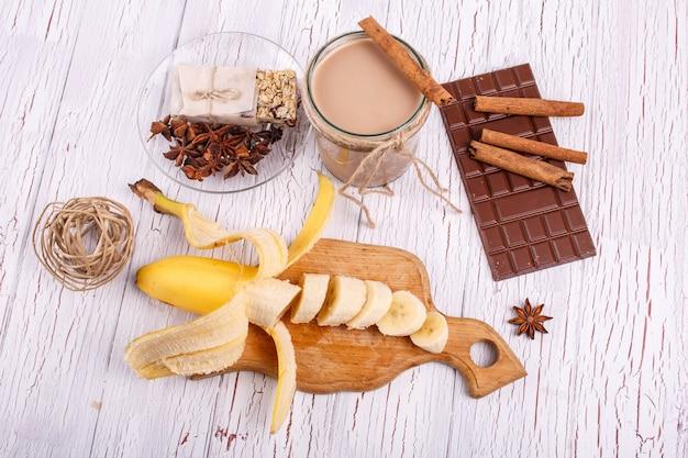 Cocto à la désintoxication brun avec des bâtonnets de cannelle, des bananes et du chocolat